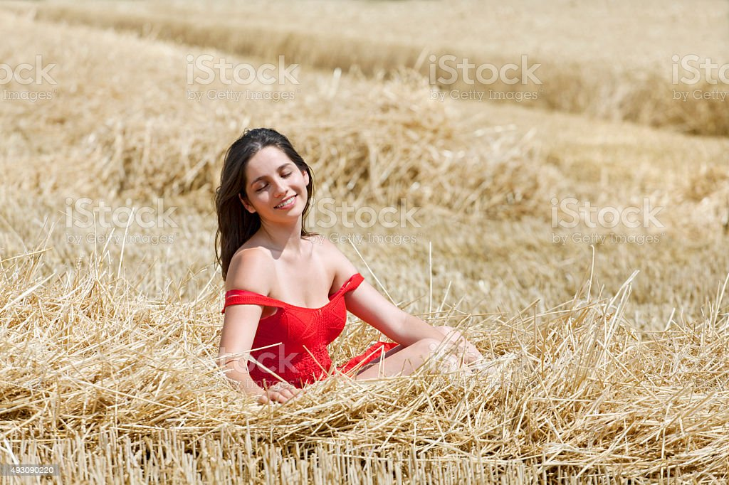 Young woman is basking in the stubble after harvesting stock photo