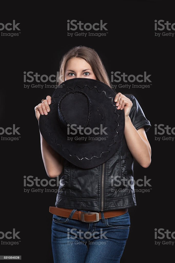 Young woman is covered or hidden behind  black cowboy hat. stock photo