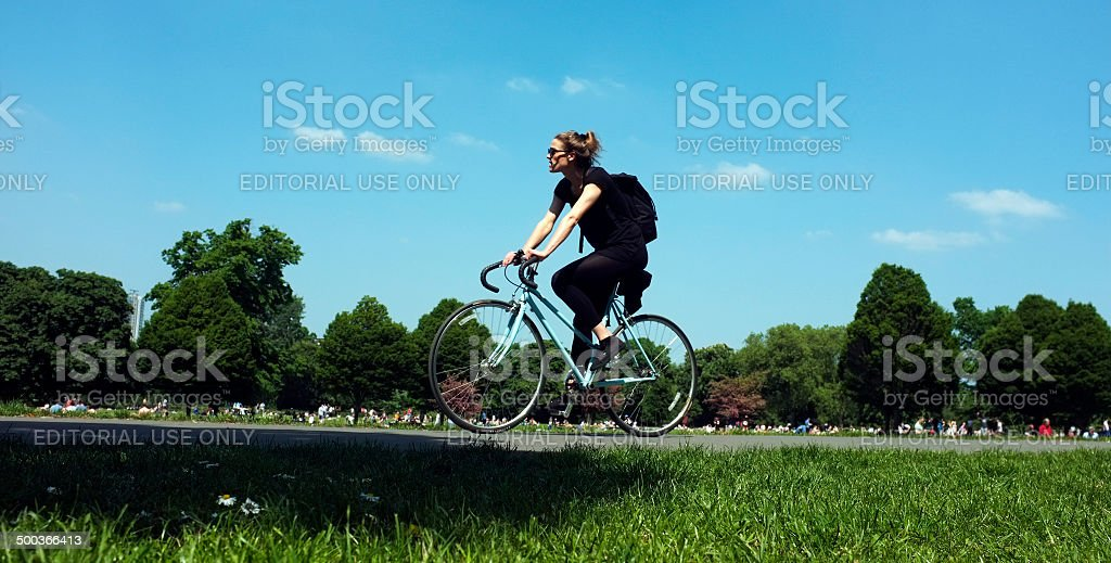 Young woman is cycling in a park stock photo