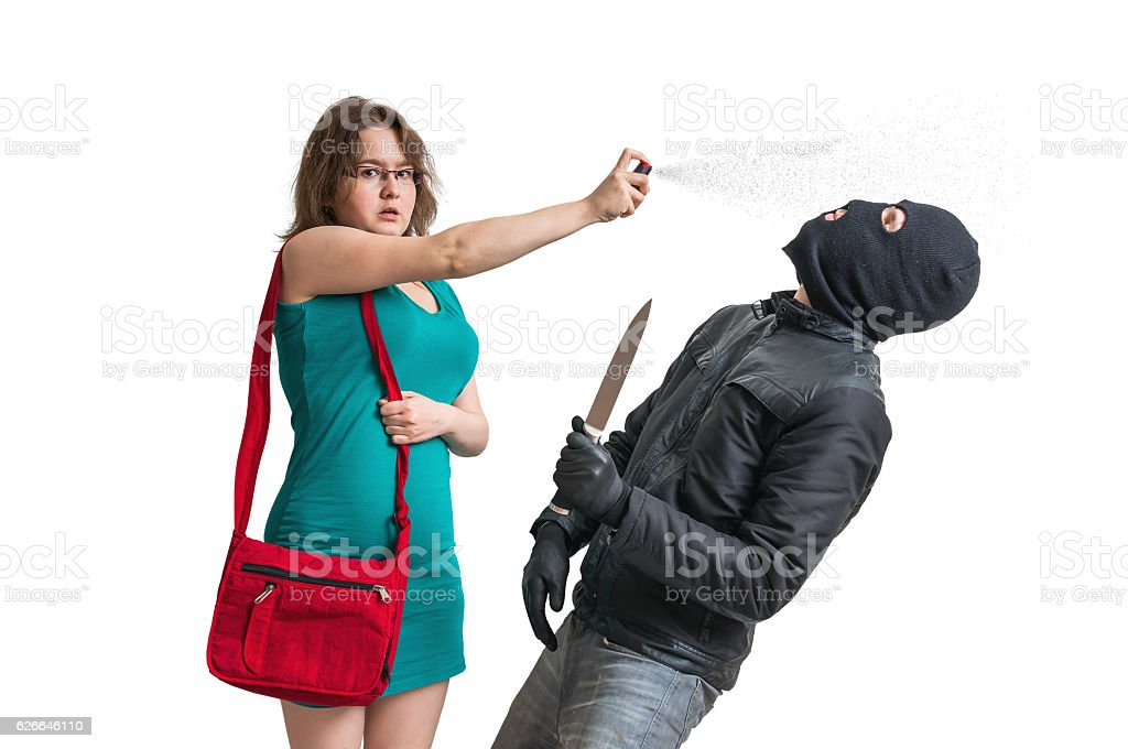 Young woman is defending with pepper spray against armed thief. stock photo