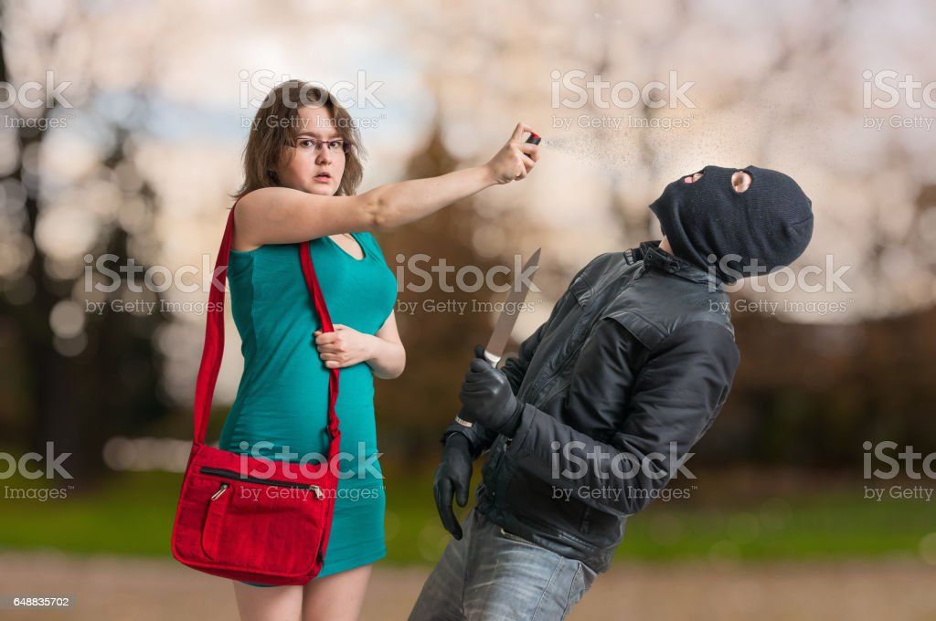 Young woman is defending with pepper spray against armed thief with knife. stock photo