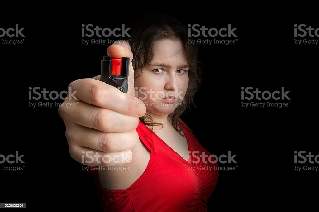 Young woman is defending with pepper spray. Self defense concept. stock photo
