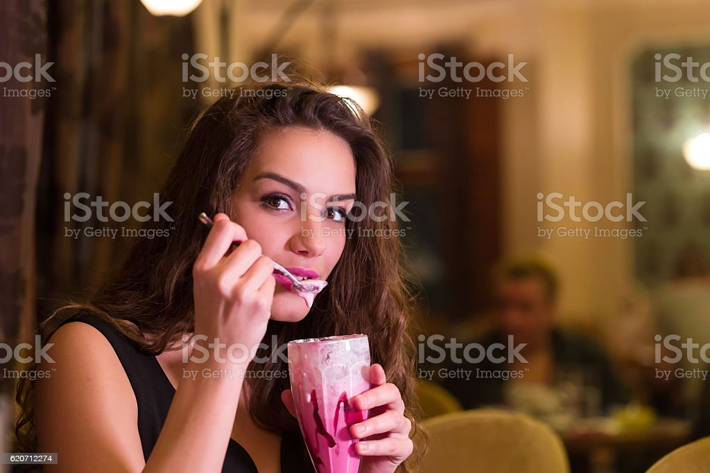 Young woman is eating whipped cream drink stock photo