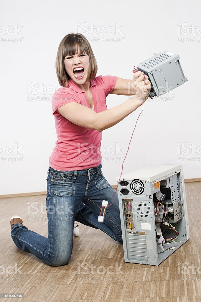 Young woman is getting mad with computer stock photo