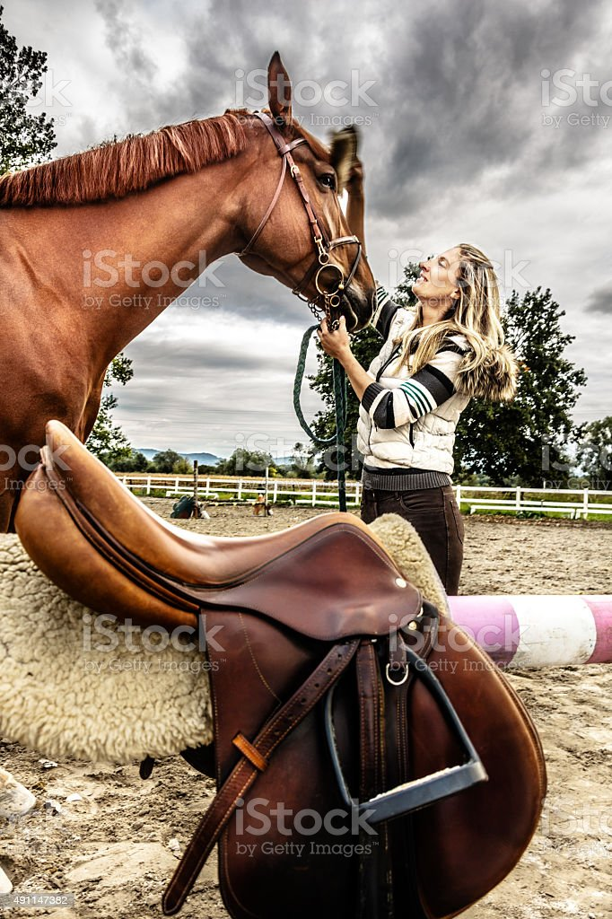 Young woman is grooming horse and preparing it for riding stock photo