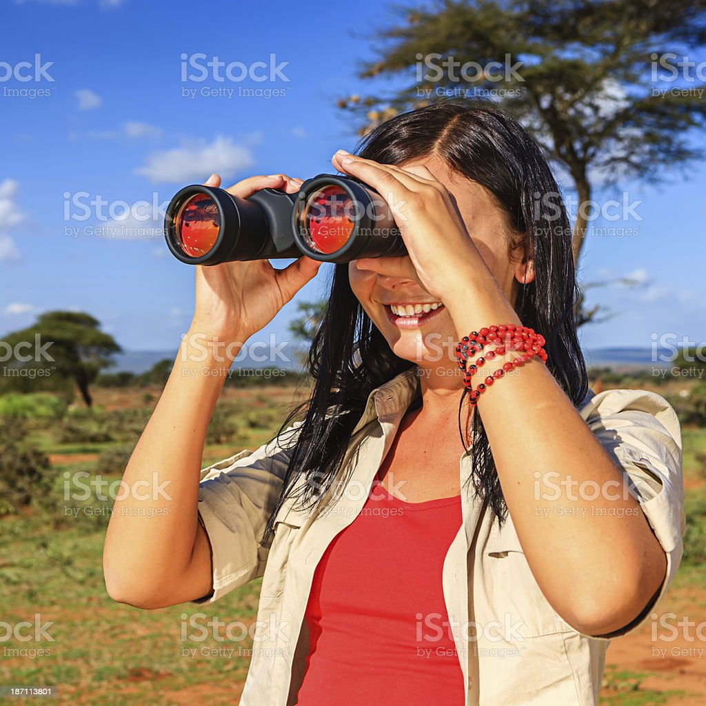 Young woman is looking through a binoculars during safari royalty-free stock photo