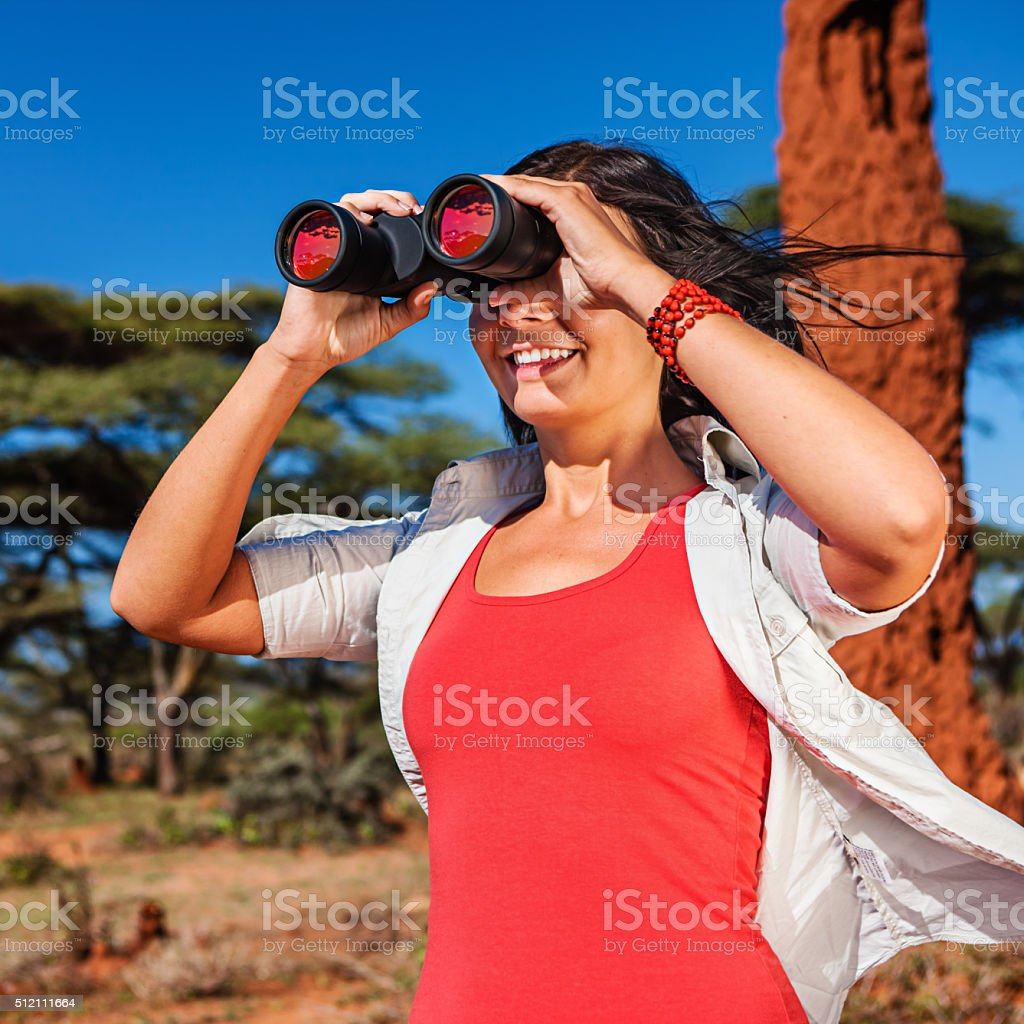 Young woman is looking through a binoculars during safari stock photo