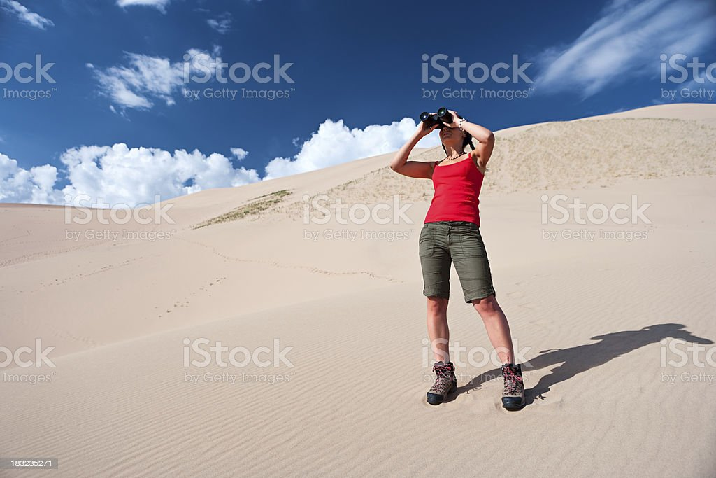Young woman is looking through a binoculars on the desert royalty-free stock photo