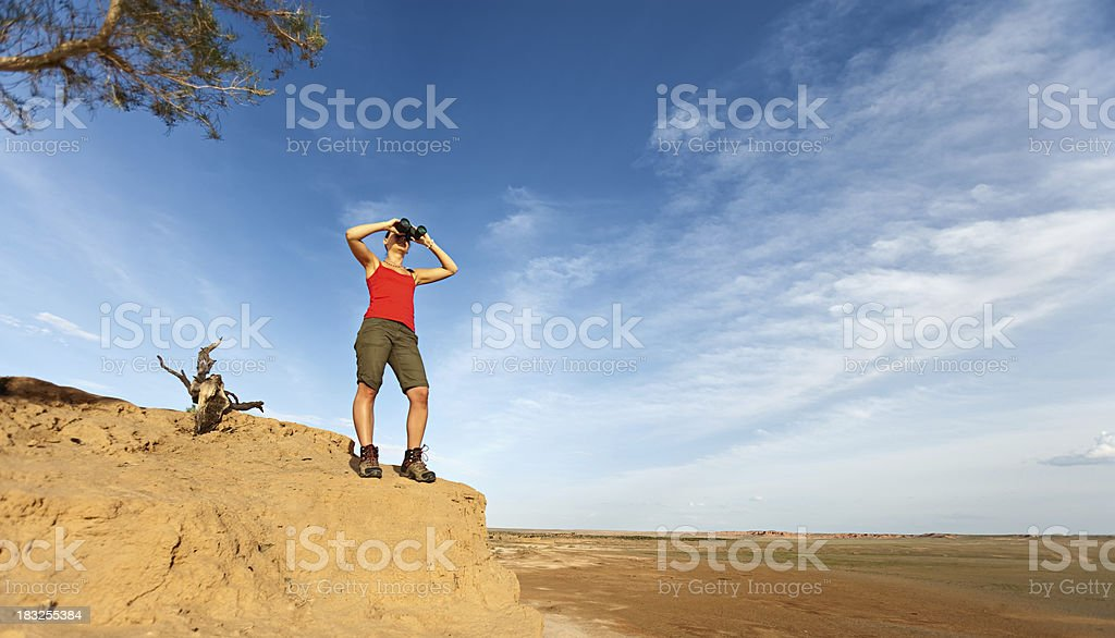 Young woman is looking through a binoculars royalty-free stock photo