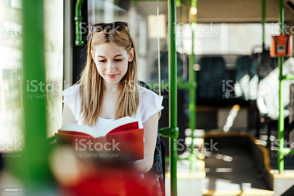 Young woman is reading a book while commuting stock photo