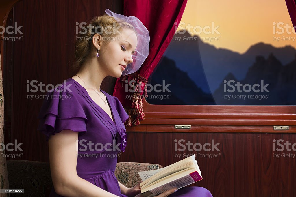 Young woman is reading the book in train stock photo