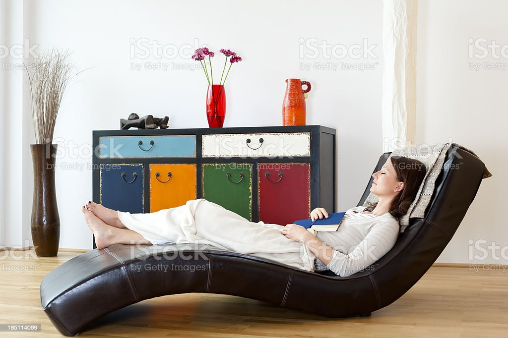 Young woman is relaxing at the couch stock photo