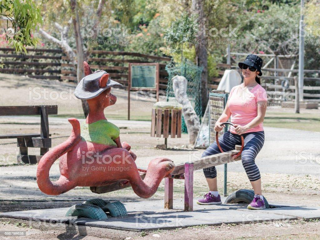 Young  woman is riding on a kangaroo-shaped swing at the Australian Zoo Gan Guru in Kibbutz Nir David, in Israel stock photo