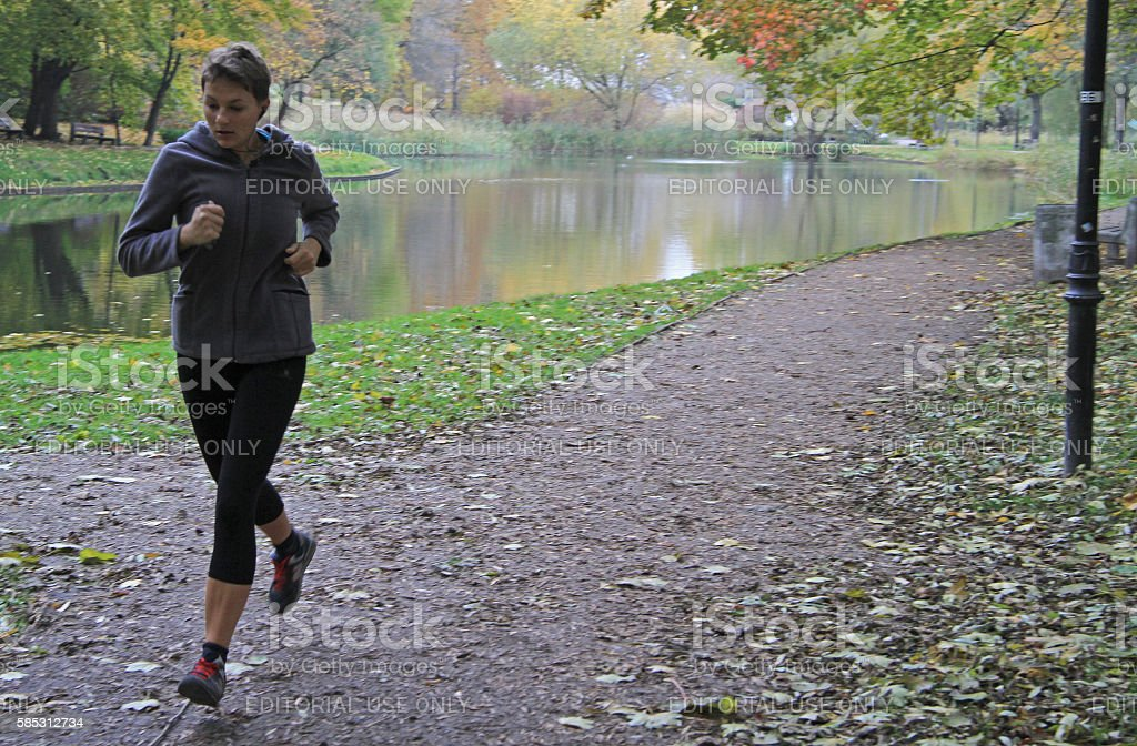 young woman is running in park of Warsaw stock photo