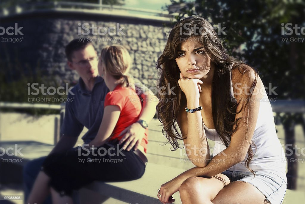 A young woman is seated near an embracing couple, frowning stock photo