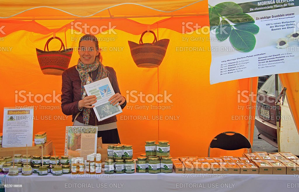 young woman is selling butter on street market stock photo