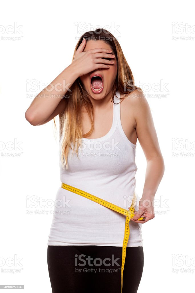 Young woman is shocked by the scope of her waist stock photo