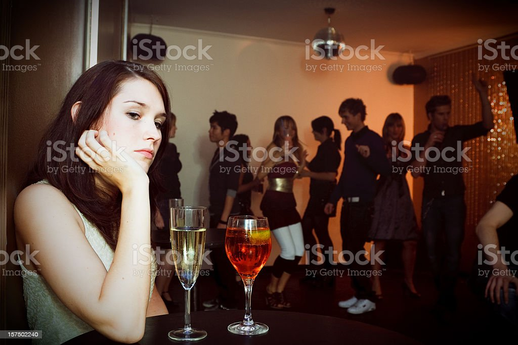 young woman is sitting alone in a nightclub stock photo