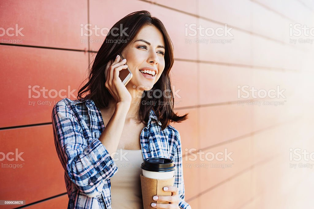 Young woman is talking by smart phone stock photo