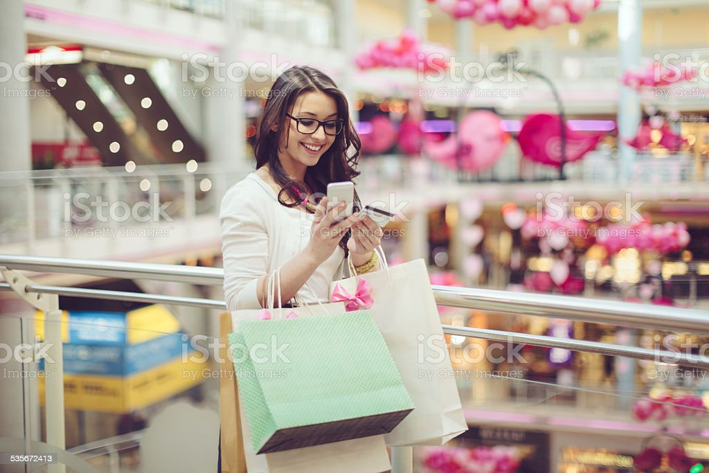 Young woman is texting in a shopping mall stock photo