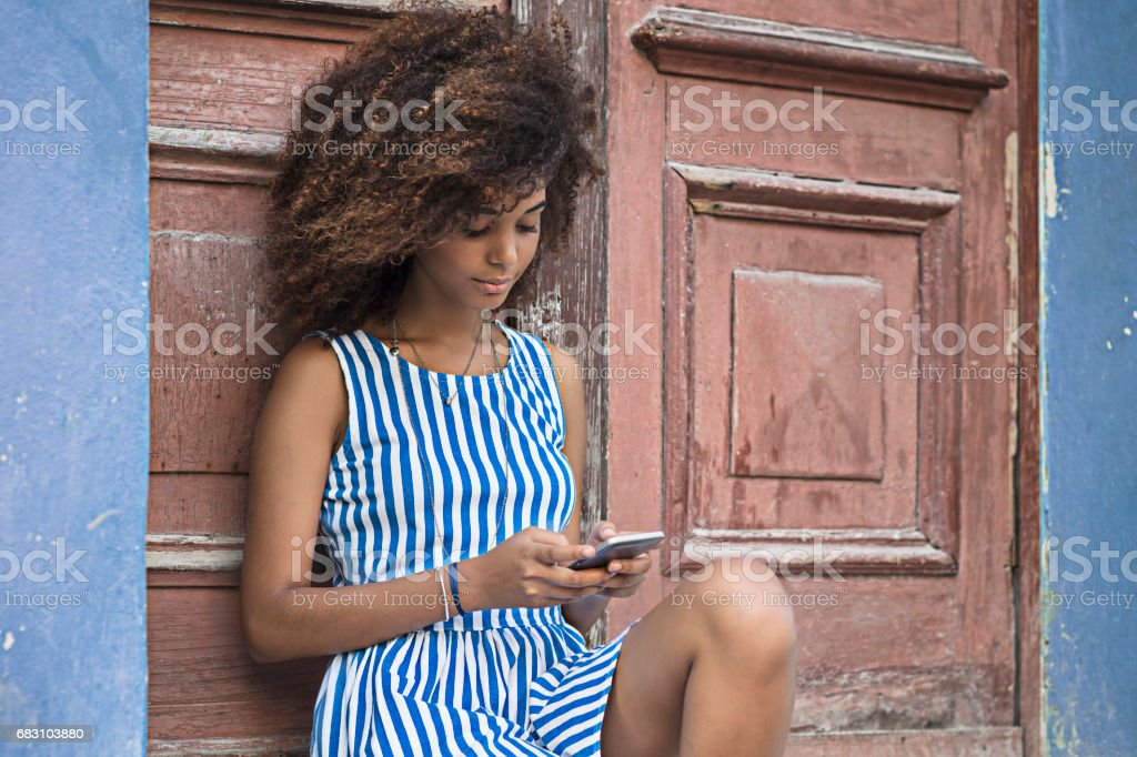 Young woman is using mobile phone against door stock photo