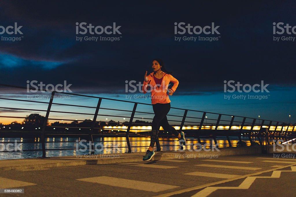Young Woman Jogging At Night Near River. stock photo