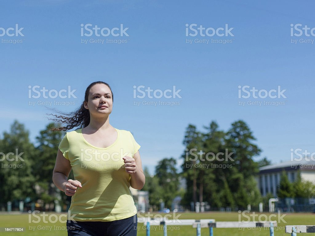 Young woman jogging at the stadium royalty-free stock photo