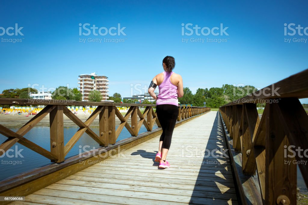 Young woman jogging cross-country running in summer seaside.  Concept fitness and healthy lifestyle stock photo