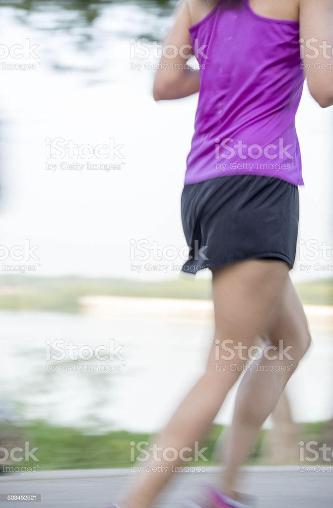 Young woman jogging in purple sports top stock photo