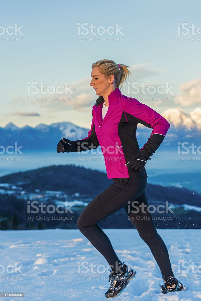 Young woman jogging in snow conditions at sunset stock photo