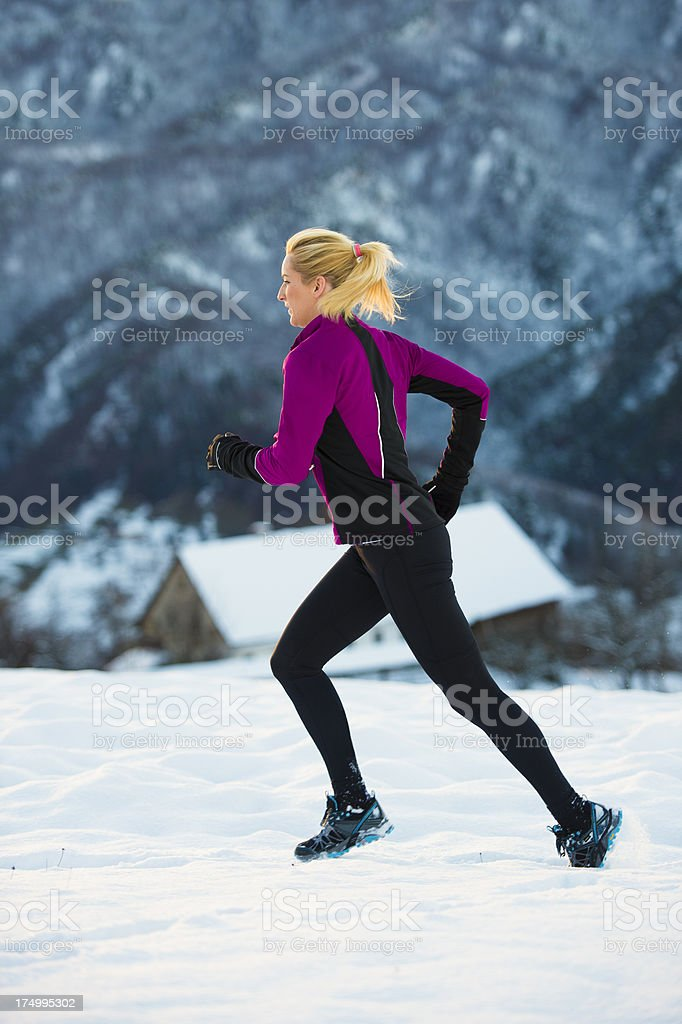 Young woman jogging in snowy conditions stock photo
