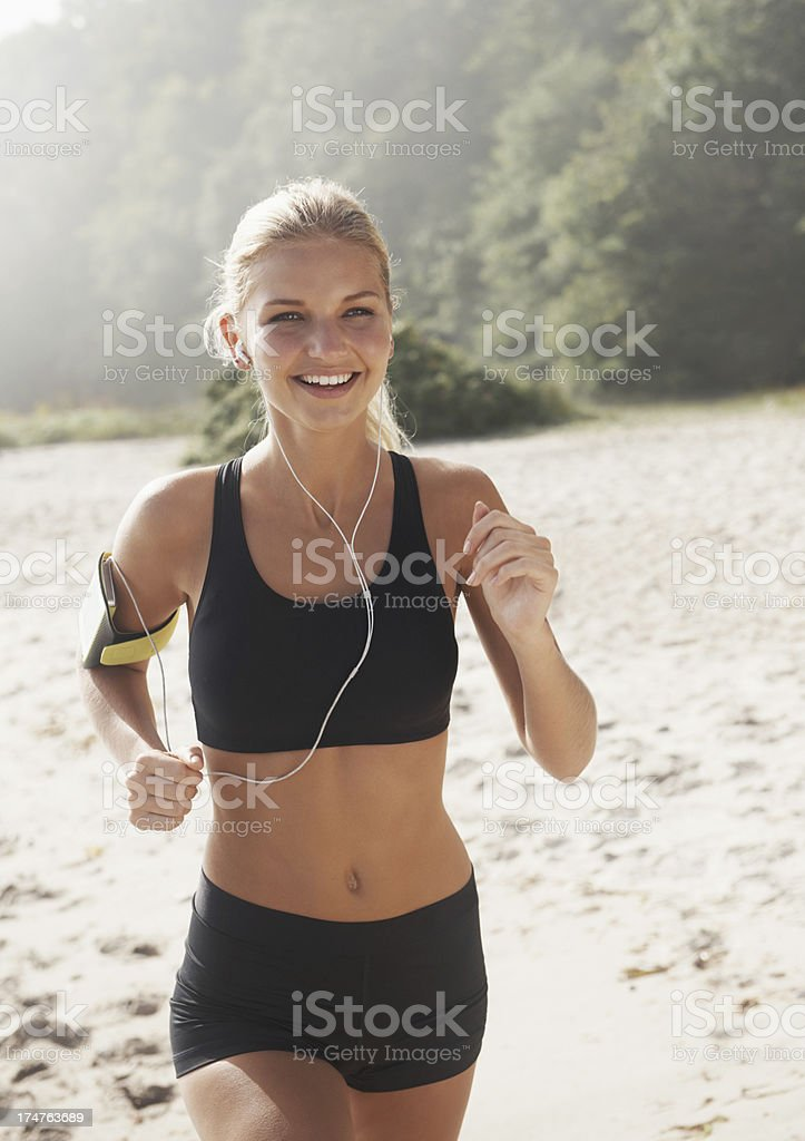 Young woman jogging in the beach and listening to music royalty-free stock photo