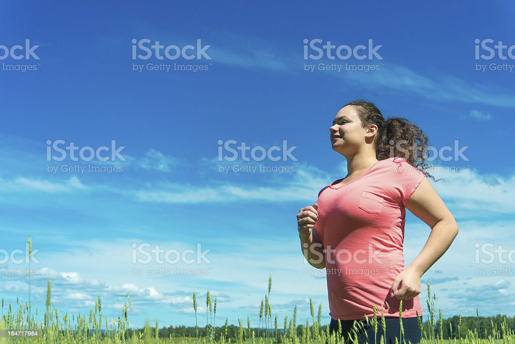Young woman jogging in wide field royalty-free stock photo