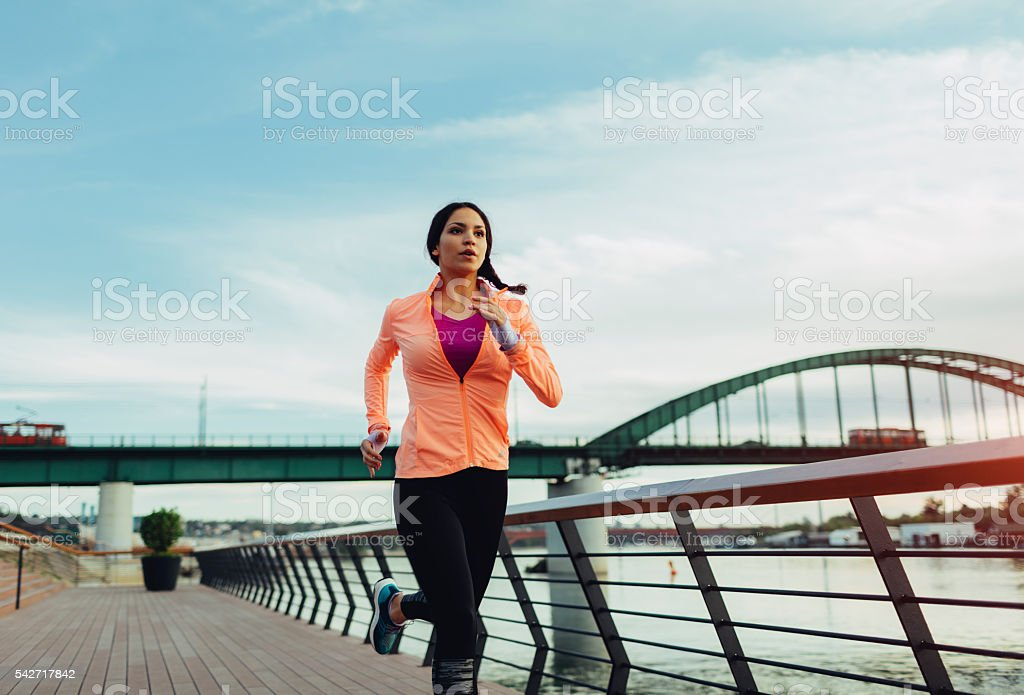 Young Woman Jogging Near River. stock photo