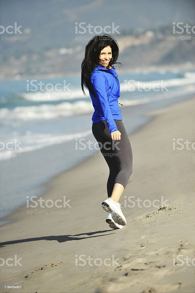 Young Woman Jogging on Beach royalty-free stock photo