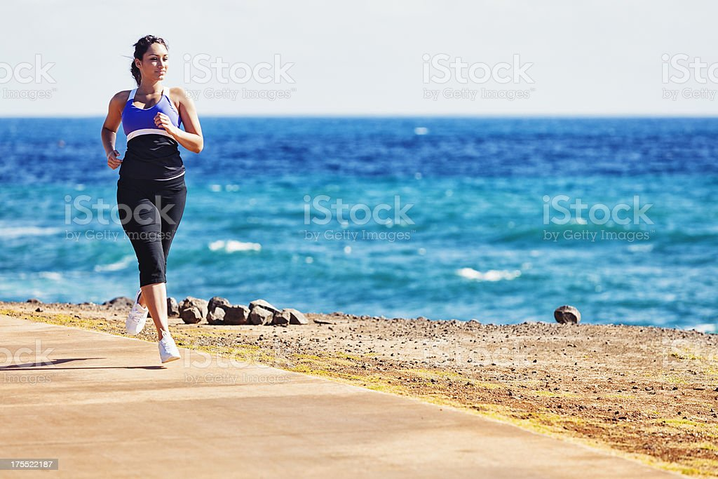Young Woman Jogging on Oceanside Path royalty-free stock photo