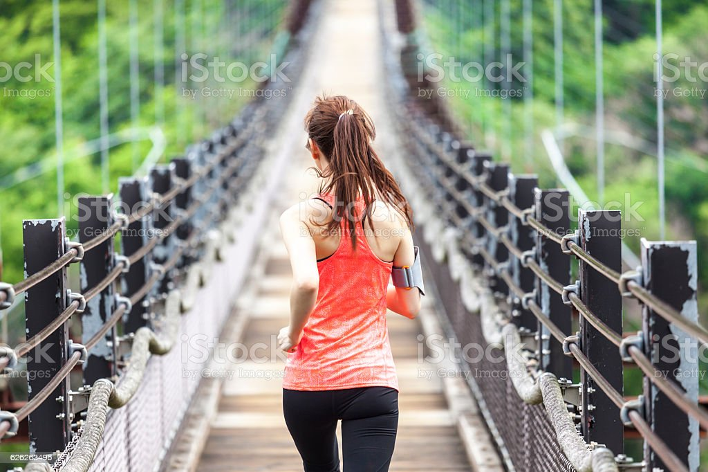 Young woman jogging on rope bridge stock photo