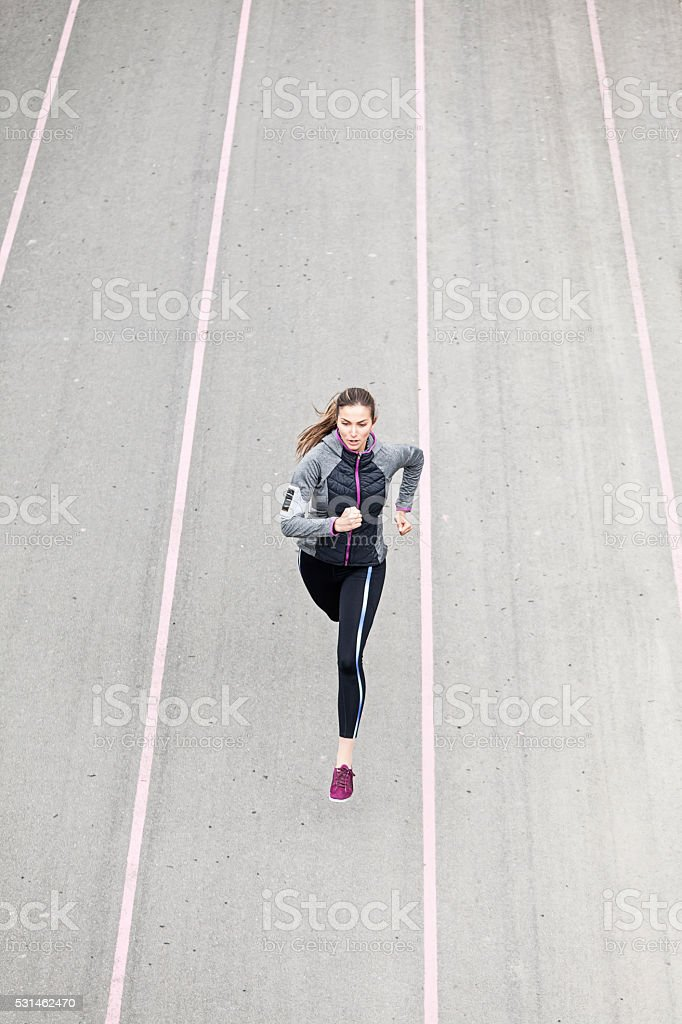 Young woman jogging on sport track stock photo