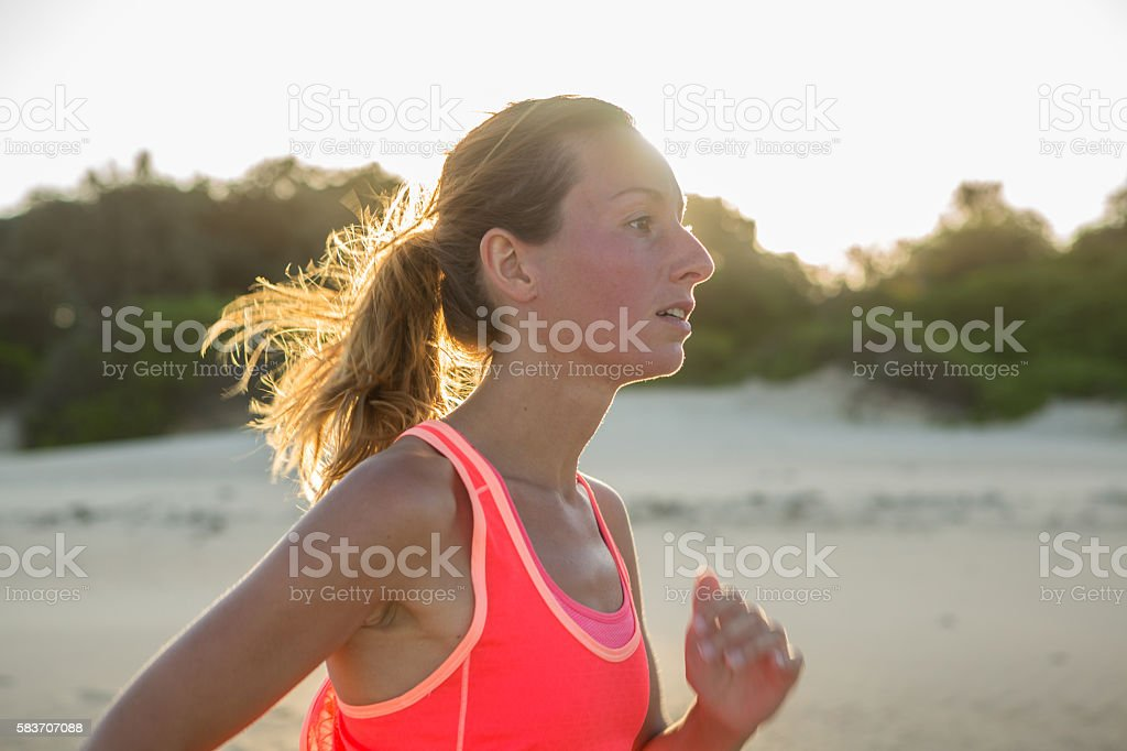 Young woman jogging on the beach at sunset stock photo