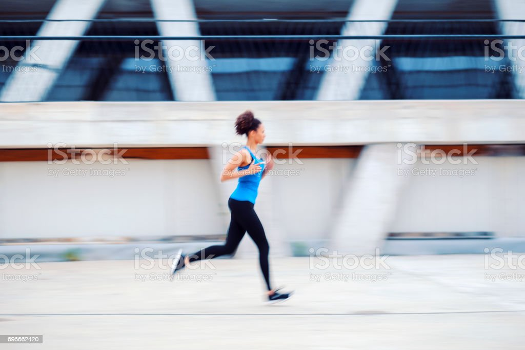 Young woman jogging on the street stock photo