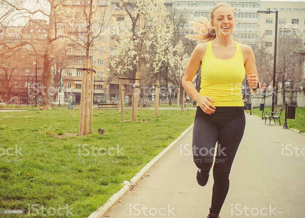 young woman jogging outdoor stock photo