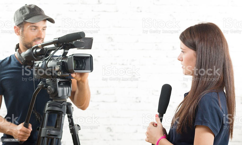 young woman journalist with a microphone and a cameraman stock photo