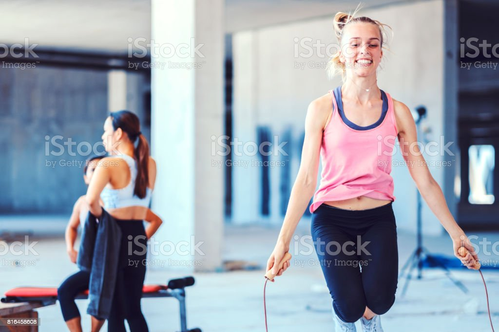 Young woman jump roping in improvised ghetto fitness stock photo