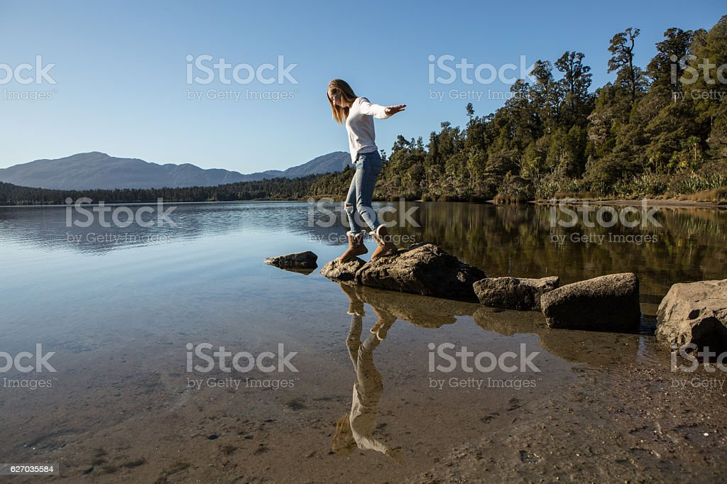 Young Woman Jumping Across Rocks in Lake stock photo