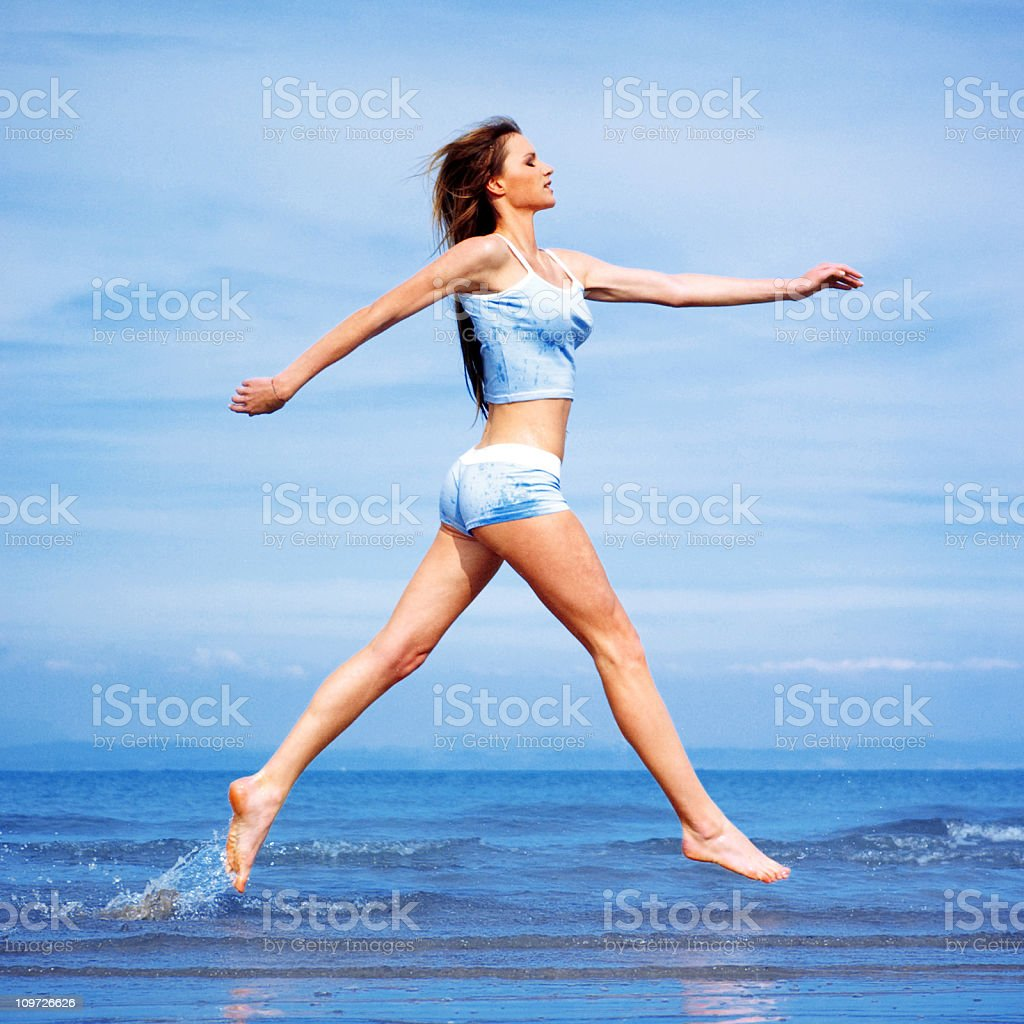 Young Woman Jumping and Running Through Water on Beach royalty-free stock photo