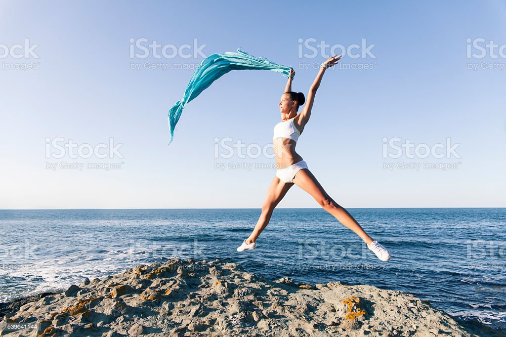 Young woman jumping and waving a blue veil stock photo