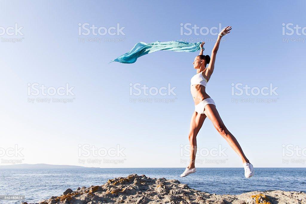 Young woman jumping and waving a sarong stock photo