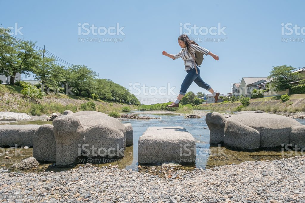 Young Woman Jumping from Turtle Stepping Stones Shortcut Across River stock photo