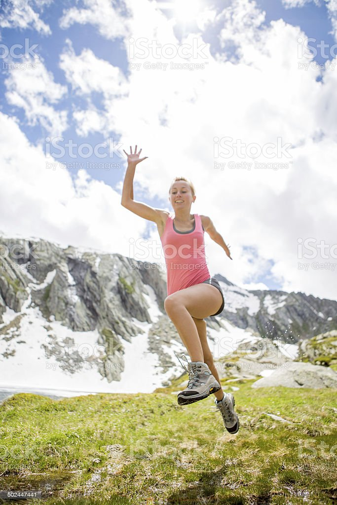 Young woman jumping in nature stock photo