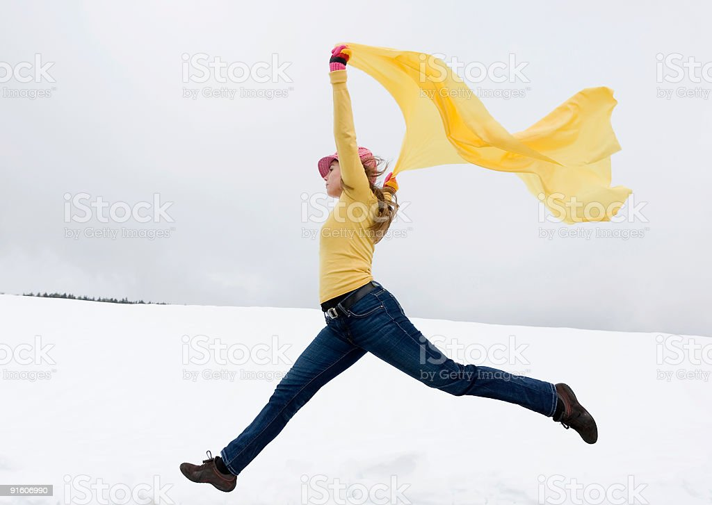 Young woman jumping in snow holding yellow scarf to wind royalty-free stock photo